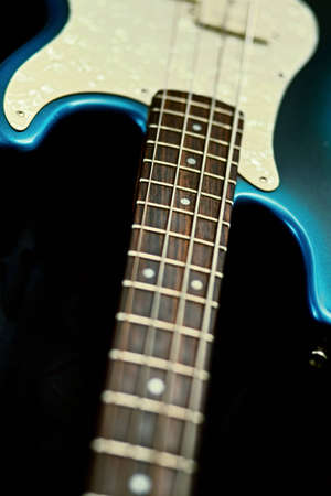 Blue and ivory guitar with neck and body exposed on a black background.  Focus on the strings and fret board.