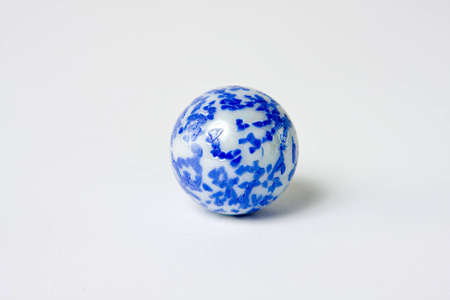 eye ball: A very interesting blue and white speckled marble set against a white background.  The marble has an interesting and unique spotted design. Stock Photo