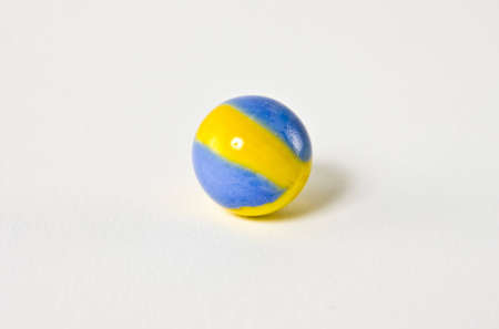 A blue and yellow swirled glass marble set against a white background.  The marble resembles the colors of the Swedish flag. Stok Fotoğraf