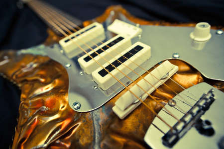 A unique and artistic custom guitar with a wonderful shot of the textured metal body and strings.