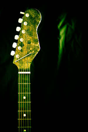 The neck and strings of a wooden guitar againts a back background.  The guitar neck has a beautiful green tint and focus.