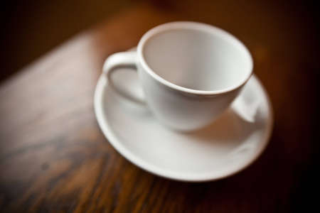 An empty white coffee mug on a small white plate.  The mug is on a cherry wood table. Stok Fotoğraf
