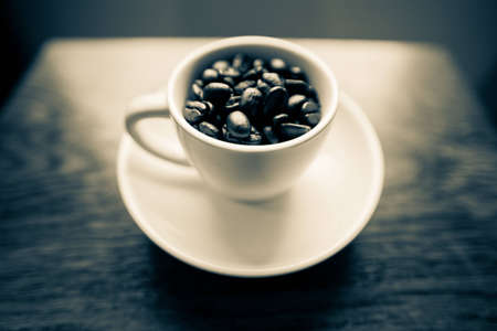 A black and white shot with a bit of a blue hue of a white coffee mug on a small white plate filled with dark roasted coffee beans.  The mug is on a cherry wood table.