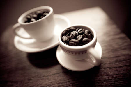 Two white coffee mugs on small white plates filled with dark roasted coffee beans.  The mugs are on a cherry wood table.