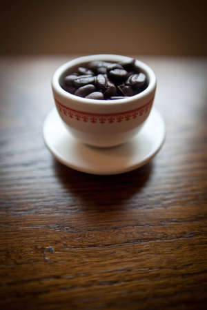 A white coffee mug with an interesting red pattern on a small white plate filled with dark roasted coffee beans.  The mug is on a cherry wood table.