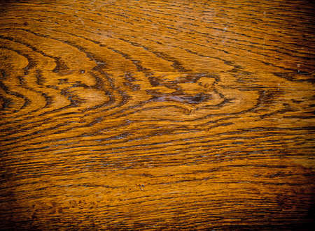 A cherry colored wood panel that could be a table or a piece of hardwood floor.  The wood piece has some wonderful grains and textures.  Lots of interesting lines.