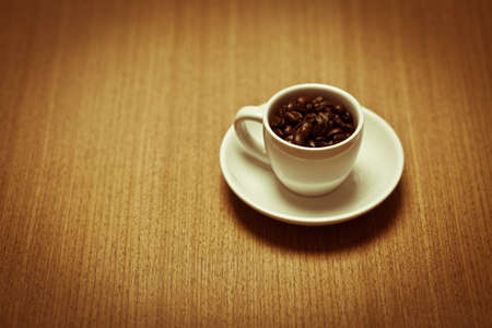 A white coffee mug on a small white plate filled with dark roasted coffee beans.