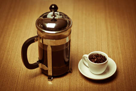 A white coffee mug on a small white plate filled with dark roasted coffee beans sitting next to a french press.  Stok Fotoğraf