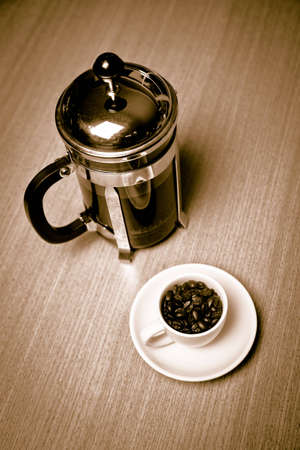 A french press sits next to a white coffee mug on a small white plate filled with dark roasted coffee beans.  The mug is on a cherry wood table.