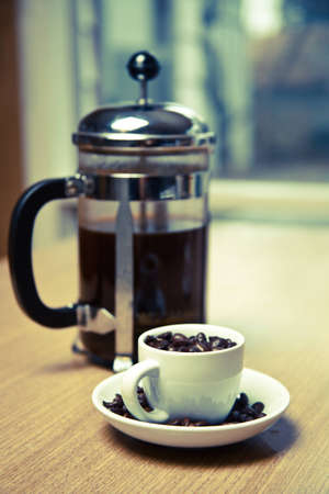 A blue hued french press and white coffee mug on a small white plate filled with dark roasted coffee beans.  The mug is on a cherry wood table.