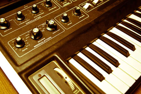 hued: A yellow hued shot of a synthesizer and its knobs, keys, and wheels.  the synthesizer is on top of a wood table. Stock Photo