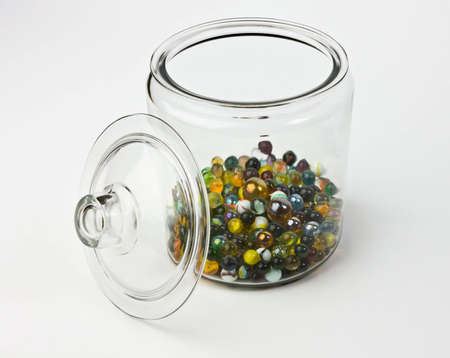 Glass jar half full of colorful glass marbles on a white background. There are a variety of different colors including yellow, green, orange, blue, black, and red.