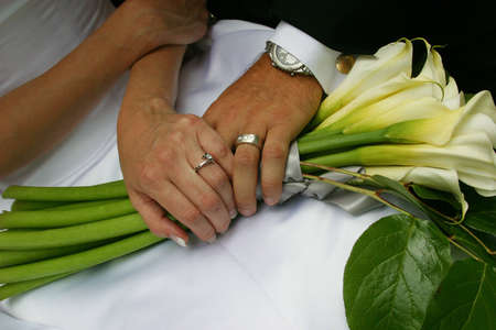 A close-up of a Newly Married Couple Holding Hands On Wedding Bouquet. You can see their newly exchanged wedding bands, as well as the brides beautiful wedding dress.