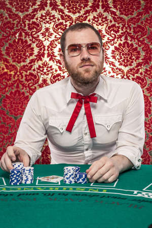 A man wearing glasses, a white shirt, and a red Texas tie sits at a blackjack table  There are stacks of blue and white chips in front of him  Editöryel