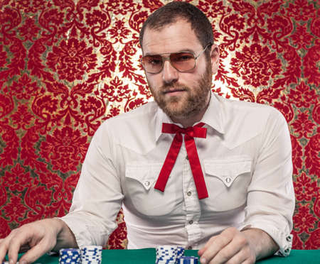 A man wearing glasses, a white shirt, and a red Texas tie sits at a blackjack table  There are stacks of blue and white chips in front of him  Stok Fotoğraf
