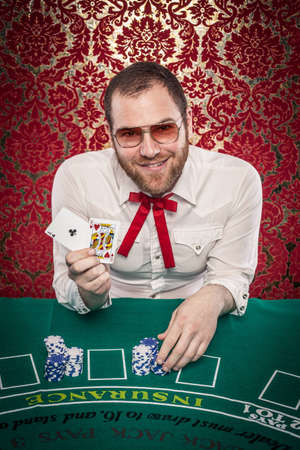A man wearing glasses, a white shirt, and a red Texas tie sits at a blackjack table  He holds up a winning hand and smiles at the camera  There are stacks of blue and white chips in front of him  Editöryel