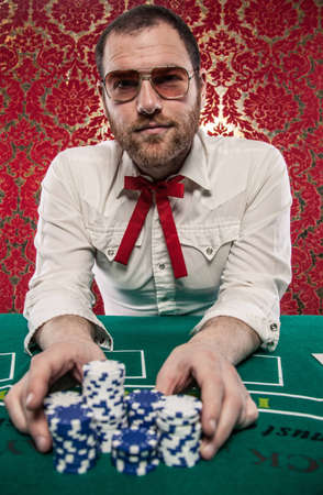 A man wearing glasses, a white shirt, and a red Texas tie sits at a blackjack table  He is making a big bet with all of his chips