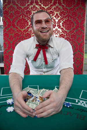 A man wearing glasses, a white shirt, and a red Texas tie sits at a blackjack table  He smiles widely as he pulls his big pile of winnings towards himself  Stok Fotoğraf