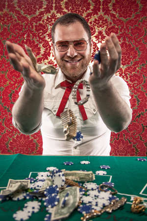 A man wearing glasses, a white shirt, and a red Texas tie sits at a blackjack table  He smiles as he tosses his winnings in the air