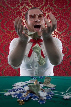 A man wearing glasses, a white shirt, and a red Texas tie sits at a blackjack table  He smiles hugely as tosses his winnings in the air