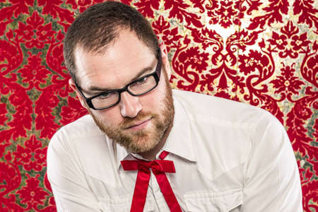 A man wearing black-framed glasses, a white shirt, and a red Texas tie sits in front of vintage red wallpaper  He leans forward confidently while looking at the camera