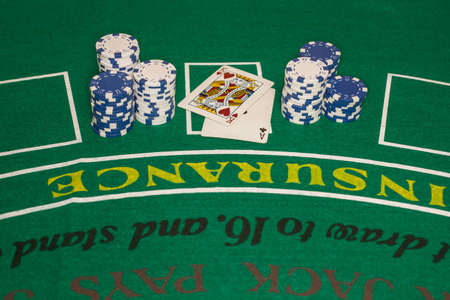 Several stacks of blue and white poker chips are arranged on either side of two playing cards on a green card table  There is upside-down lettering on the card table