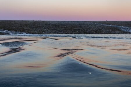 soft, long water surface ripples in a pink and silber sunset light, with a shiny horizon