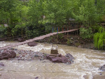 wooden bridge over the Ourika river with rising floodwater