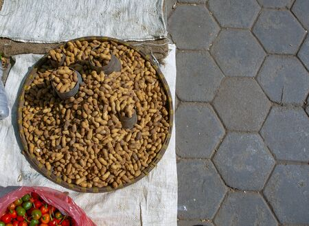 fresh peanuts were placed in a round basket made of palm tree leaves  at a farmer market in Nepal, Kathmadu 写真素材