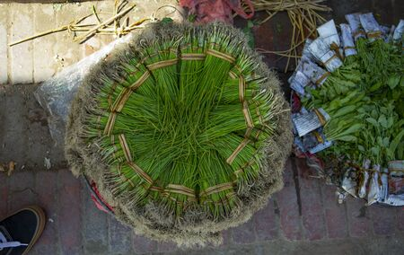 bundle of asian herbs on a round plate on an asian farmers market 写真素材