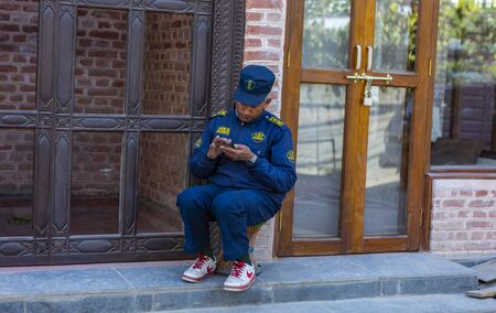 Kathmandu, Nepal-November 02,2017:security guard is sitting inattentive while texting on a cell phone Editöryel
