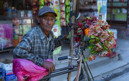 Kathmandu, Nepal-November 02,2017:smiling old Riksha driver takes a break in the streets of Kathmandu