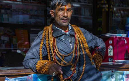 Kathmandu, Nepal-November 02,2017:Nepali man with a scar face is selling  prayer chains Editöryel
