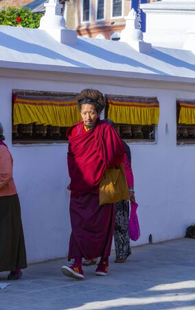 Kathmandu, Nepal-November 02,2017:religious Tibetan monk and women is walking around the Stupa of Bodnath in Kathmandu