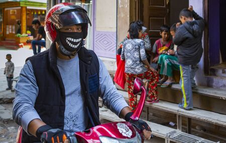 Kathmandu, Nepal_ November 02,2017:young asian man on a motorbike with a funny breathing protection around his face Editöryel