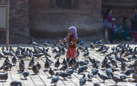 Kathmandu, Nepal-November 02,2017:young asian girl surrounded by pigeons on a square in Kathmandu Editöryel
