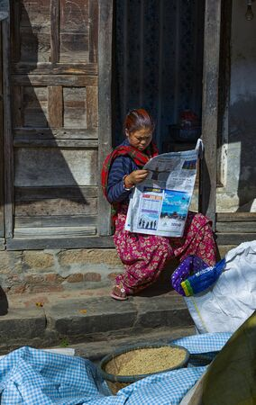 Kathmandu, Nepal-November 02,2017:Nepalese women in traditional clothes is reading a newspaper in a door entrance on a sunny day