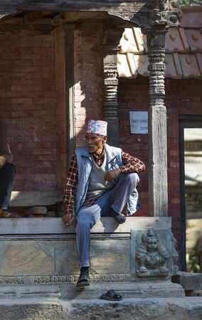 Kathmandu, Nepal-November 02,2017:senior Nepali man  smoking relaxed a cigarette outdoor a temple in a non smoking zone Editöryel