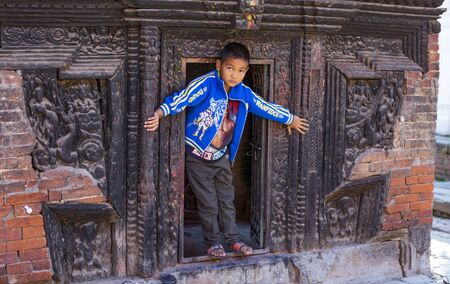 Kathmandu,  Nepal-November 03,2017:young serious looking asian boy is presenting proudly himself while playing in a temple Editöryel