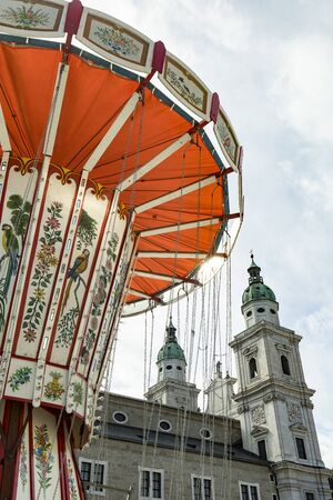 Salzburg, Austria-September 24,2017: Cathedral of Salzburg with a colorful carousel in the foreground