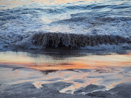 close up from a wave crashing on a sandy beach with sun reflection in the water