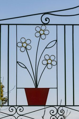 gateway with an iron metal gate in the retro design  of the sixties with flowerpot