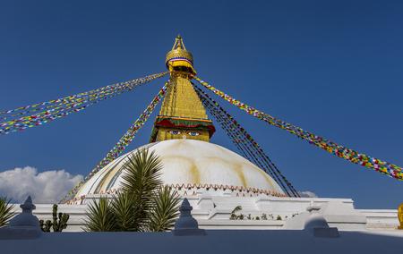 golden roof of the Stupa of Bodnath in Kathmandu with Tibetan flags 報道画像
