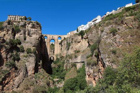 City of Ronda in Andalusia on top of a rock, one of the most typical white village in the region, with its amazing bridge Stock Photo