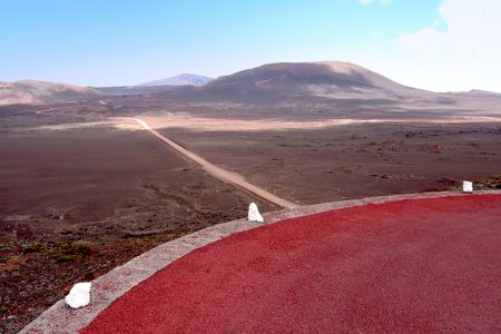 Across a sandy plain made of volcanic dust, a road has been built