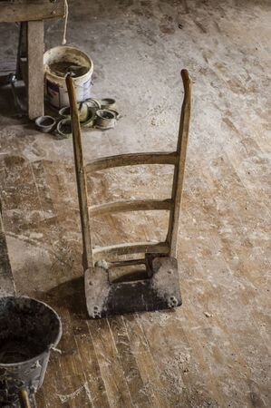 Vintage hand barrow standing upright on wooden floor, in flour mill