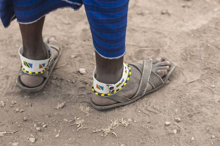 Traditional tribal bead work worn around ankle by masai man, also wearing very old and worn sandals. Tanangire National Park, Tanzania