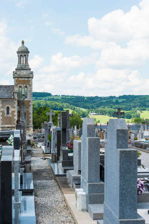 Brittany, France, June 2017. Portrait shot of old Cemetery with  headstone in a row with green meadows in the distance and blue cloudy sky in rural France Editorial