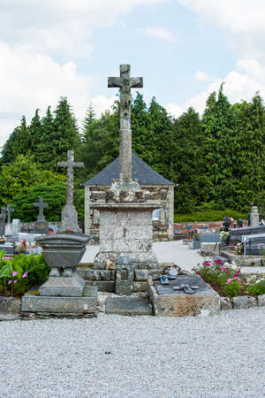 Brittany, France, June 2017.Portrait shot  of old Cemetery with  stone graves and stone crosses, with flowers in circle grave and blue cloudy sky in rural France Editorial