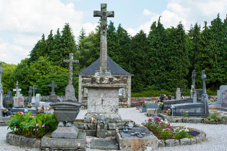 Brittany, France, June 2017. Old Cemetery with  stone graves and stone crosses, with flowers in circle grave in rural France